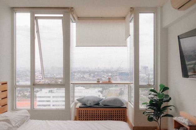 Dormitorio loft acogedor de la vida real en apartamento pequeño con vista a la ciudad