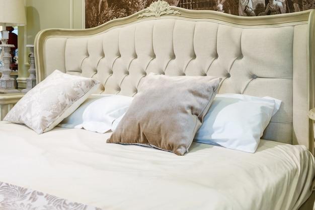 Dormitorio moderno con juego de almohadas en cama clásica.