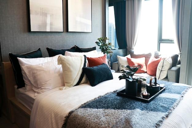 Un dormitorio moderno con muchas almohadas y cojines en la cama y el sofá.