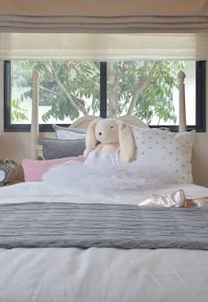 Dormitorio de niña con zapatillas de ballet y muñecas en la cama en casa