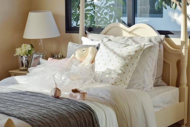 Dormitorio para niñas con ballet y muñecas en la cama en casa
