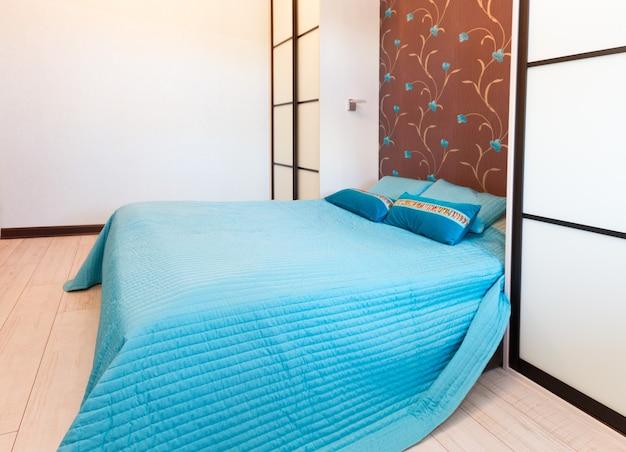 Dormitorio vacío moderno con cama doble y cuna azul