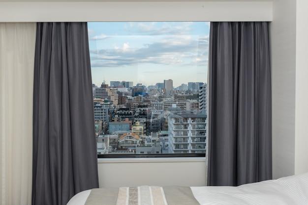 Dormitorio con ventana de cortina y edificio de ciudad.