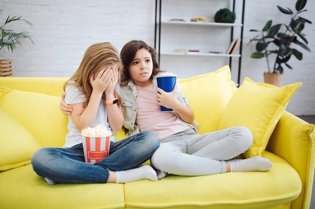 Dos adolescentes asustados se sientan en el sofá amarillo y miran una película. primera chica cubre la cara con las manos. segunda mirada asustada. ella tiene una taza de coca en la mano. la primera niña tiene un tazón de palomitas de maíz.