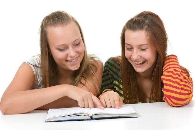 Dos adolescentes sonriendo y leyendo el libro aislado en blanco