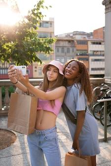Dos adolescentes tomando selfie después de una juerga de compras mientras sostiene bolsas