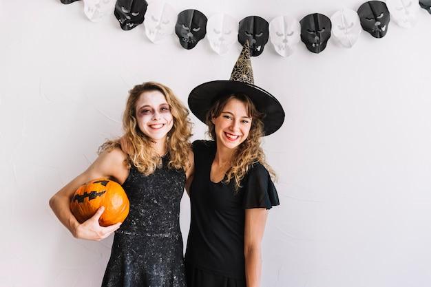 Dos adolescentes en trajes de halloween abrazando sosteniendo calabaza