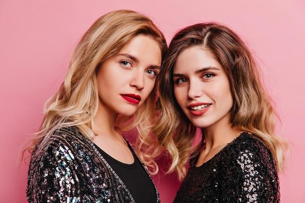 Dos adorables chicas posando con una sonrisa suave en la pared rosa. modelos femeninos complacidos