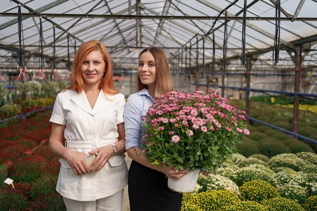Dos adorables damas posando con un ramo de crisantemos rosados en una hermosa casa verde en flor con techo de cristal.