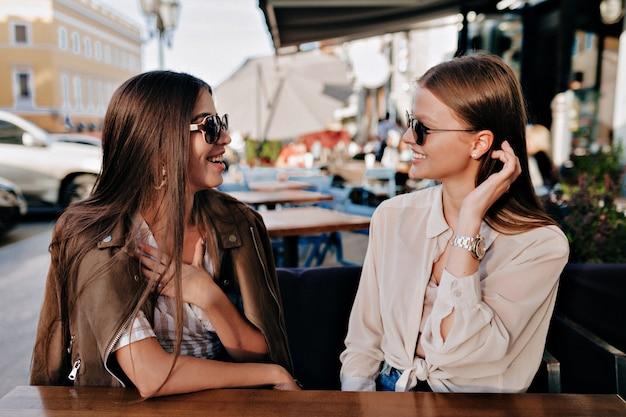 Dos adorables ladis sonrientes con gafas de sol sentados y hablando felizmente con un amigo en la terraza al aire libre de verano.