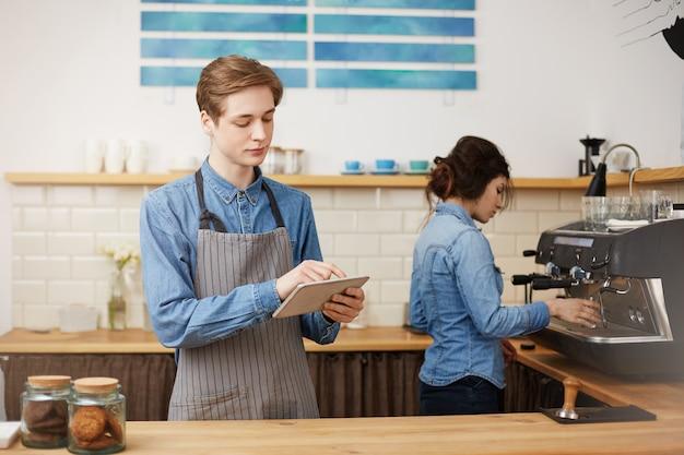 Dos alegres baristas con elegante uniforme de trabajo en la barra del bar.
