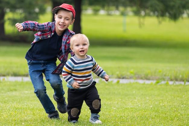 Dos alegres hermanos de diferentes edades se divierten, corren por el campo verde en un cálido día de verano.