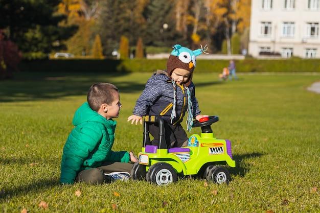 Dos alegres hermanos-niños de diferentes edades se divierten jugando con un gran jeep en silla de ruedas en un campo verde en un cálido día de verano