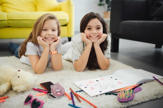 Dos alegres jóvenes adolescentes acostado en la alfombra y plantean. las chicas se ven bien y sonríen. dibujan en papel. las niñas se toman de las manos debajo de la barbilla.