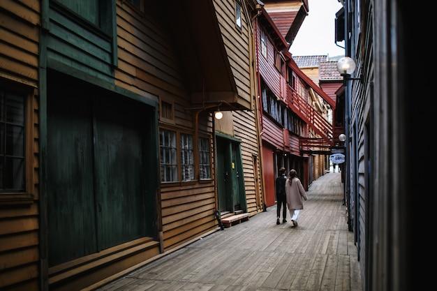 Dos amantes caminan por un callejón de madera, tomados de la mano