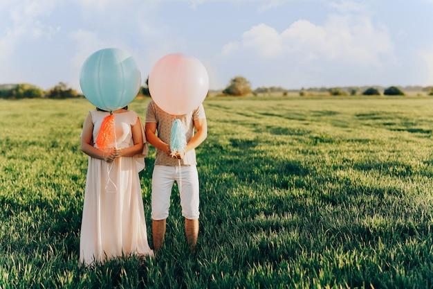Dos amantes de los jóvenes de pie en el campo con bolas de colores de helio