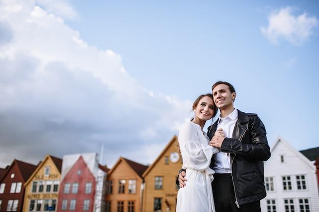Dos amantes se paran contra el fondo del casco antiguo de la ciudad de bergen