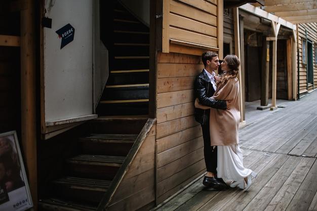 Dos amantes se paran en un viejo callejón de madera