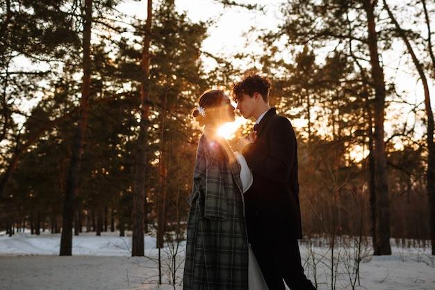 Dos amantes de pie en un bosque de invierno con el telón de fondo de la puesta de sol. sesión de fotos de boda