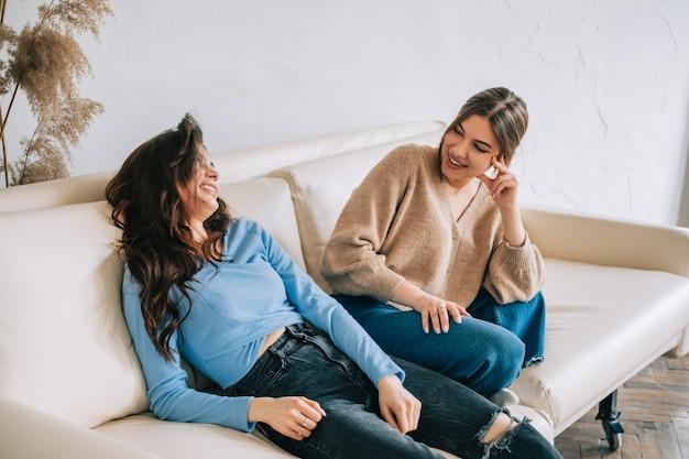Dos amiga alegre mujer sentada en un sofá y hablando entre sí