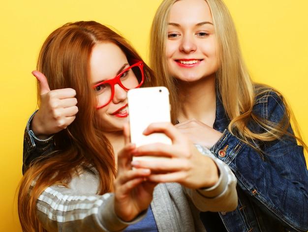 Dos amigas adolescentes en traje de hipster hacen selfie en un teléfono