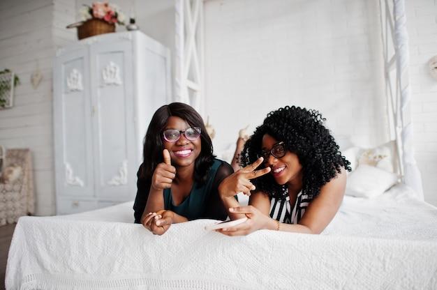 Dos amigas africanas usan anteojos acostados en la cama sala blanca interior y mirando el teléfono móvil. muestran el pulgar hacia arriba.