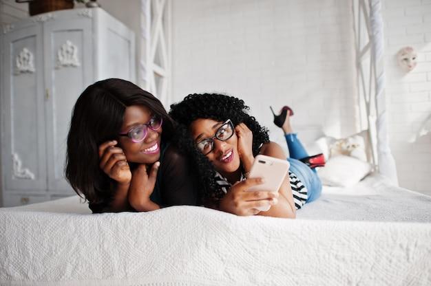Dos amigas africanas usan anteojos acostados en la cama sala blanca interior y mirando el teléfono móvil.