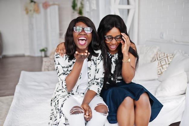 Dos amigas africanas usan anteojos en una habitación blanca interior, sentados en la cama.