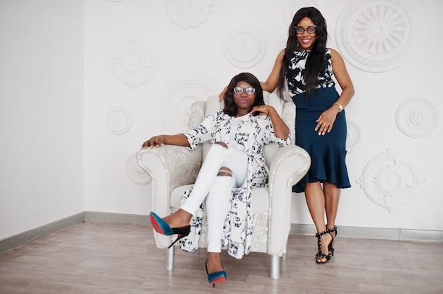 Dos amigas africanas usan anteojos que presentan una habitación blanca interior. uno de ellos sentado en una silla suave.
