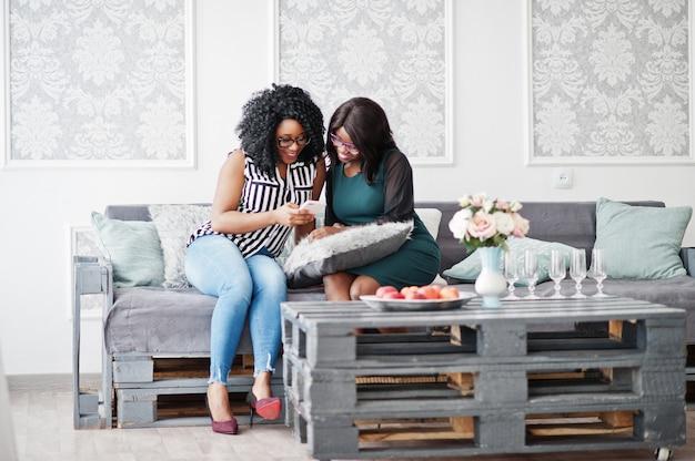 Dos amigas africanas usan anteojos sentados en la sala blanca interior del sofá y mirando el teléfono móvil.