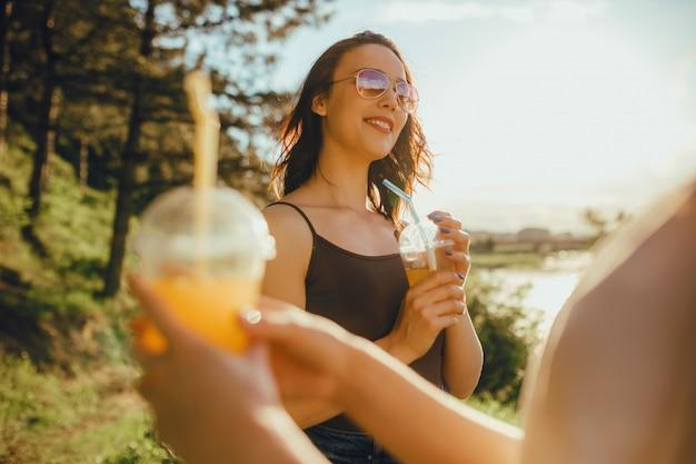 Dos amigas agradables, divirtiéndose en el verano, bebiendo jugo en gafas de sol, en camisa blanca y negra, en la naturaleza, al atardecer, expresión facial positiva, al aire libre