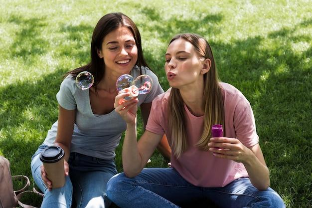 Dos amigas al aire libre soplando burbujas
