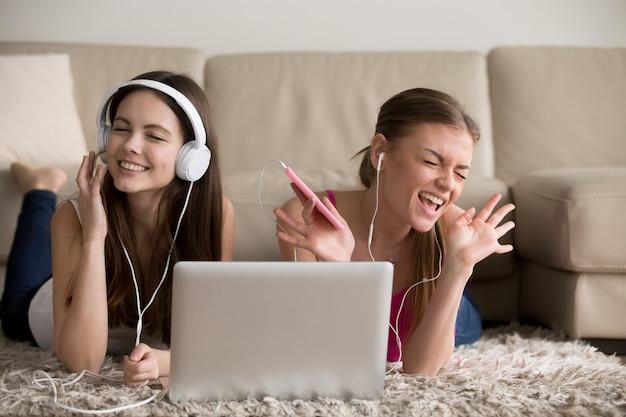 Dos amigas en auriculares divirtiéndose en casa.