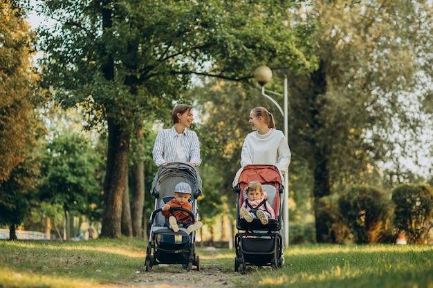 Dos amigas caminando con cochecitos de bebé y sus hijos en el parque