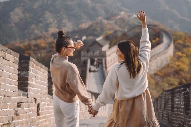 Dos amigas caminando a lo largo de la gran muralla china cerca de beijing entarnce