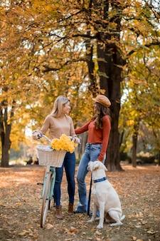Dos amigas caminando en el parque otoño amarillo con perro y bicicleta