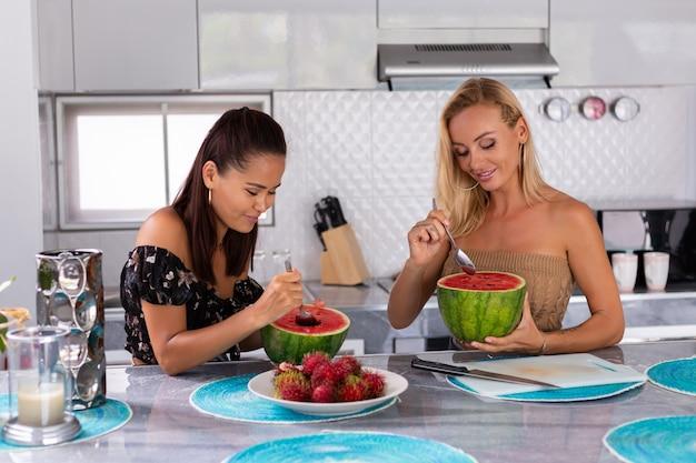 Dos amigas comiendo frutas tropicales de sandía y rambután en la cocina