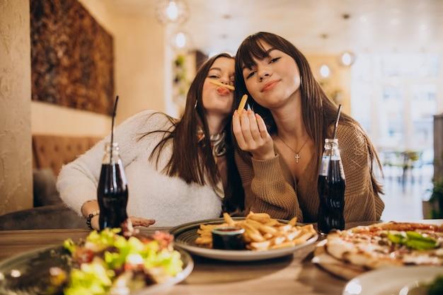 Dos amigas comiendo pizza en un café