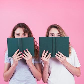 Dos amigas cubriendo su rostro con el libro de tapa verde sobre fondo rosa
