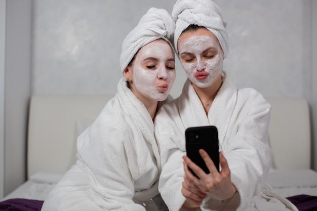 Dos amigas divertidas en albornoces, mascarillas y toallas en la cabeza se toman selfies en el teléfono. foto de alta calidad