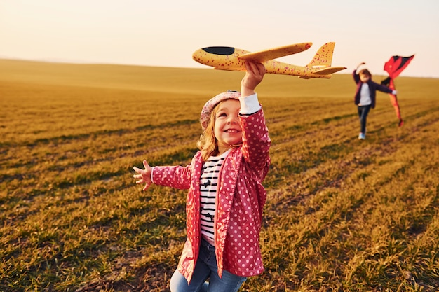 Dos amigas se divierten juntas con un cometa y un avión de juguete en el campo durante el día soleado