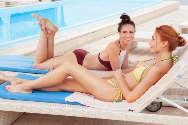 Dos amigas encantadoras relajantes junto a la piscina