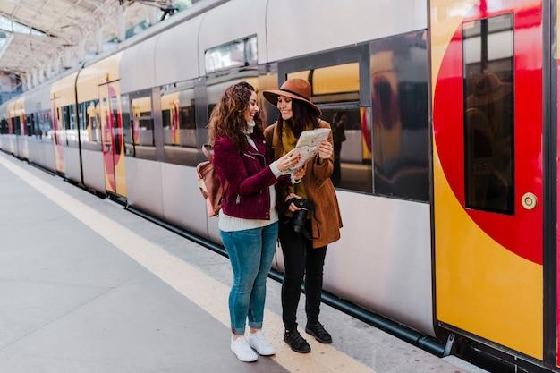 Dos amigas en la estación de tren esperando tomar un tren y viajar. leer un mapa y divertirse.