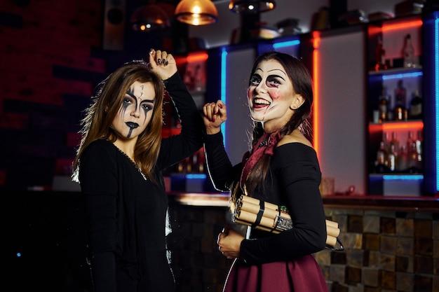 Dos amigas están en la fiesta temática de halloween con maquillaje aterrador y disfraces con bomba de tiempo.