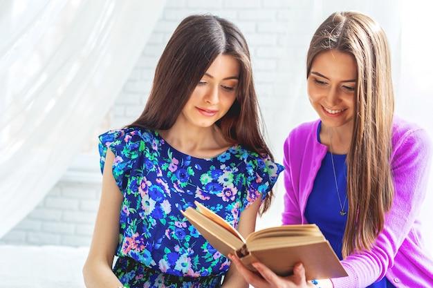 Dos amigas están mirando el libro en la cama en casa