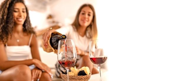 Dos amigas felices celebrando en casa vertiendo vino tinto en las copas en efecto de enfoque selectivo y espacio de copia. joven mujer caucásica brindando con su mejor amiga hispana bebiendo alcohol