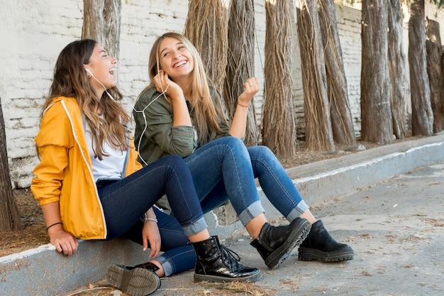 Dos amigas felices compartiendo auriculares para escuchar música.