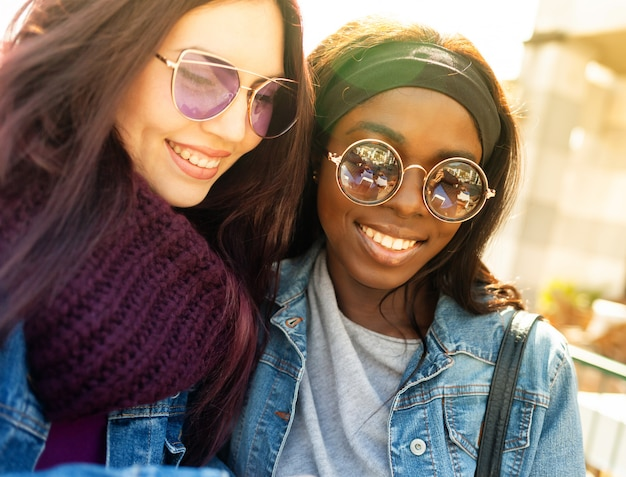 Dos amigas felices de etnia caucásica y africana.