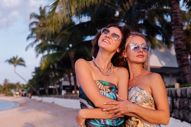 Dos amigas felices con gafas de sol de vacaciones en un país tropical
