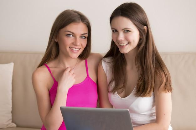Dos amigas felices juntas usando laptop en casa